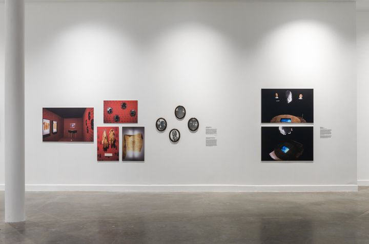Photographic works of early installations by Michael Richards are lined up along a white wall in the exhibition space.