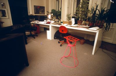 A red stool-shaped sculpture by Mit Jai Inn photographed in a domestic environment, as part of the artist's graduation exhibition.