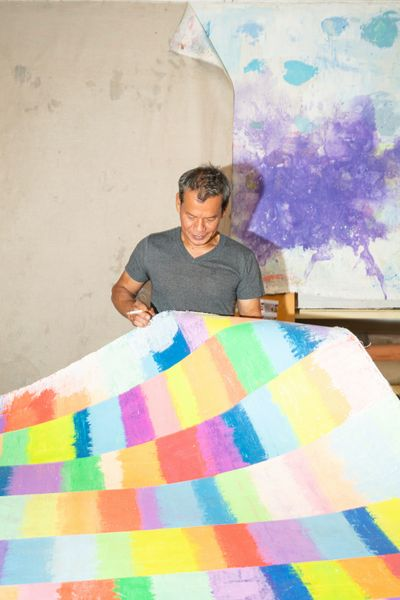 Mit Jai Inn is photographed in his studio holding up a large unstretched canvas that is covered in expressive rectangles of different colours.