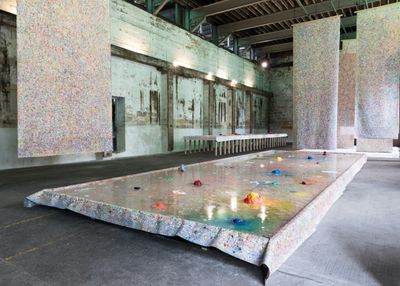 A photograph of an industrial exhibition space features a large unstretched canvas draped over a low pedestal and filled with water, with little mounds of coloured pigment dispersed through it. Above the canvas, hanging scrolls feature drips and lines of colour.