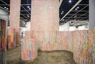 Massive, curling unstretched canvases take up the space of the exhibition hall at Art Basel in Hong Kong in 2019. Some are hanging from the ceiling and some are curved in the exhibition, standing upright on the floor. The canvases are covered in lines and drips of colour, including pinks, yellows, fuchsia, and light blue.