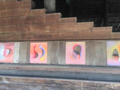 Small light pink canvases are pinned in a line across aged wood. Each pink canvas has a curvilinear opening, and surrounding the opening colours vary from yellow, orange, and light blue to purple.