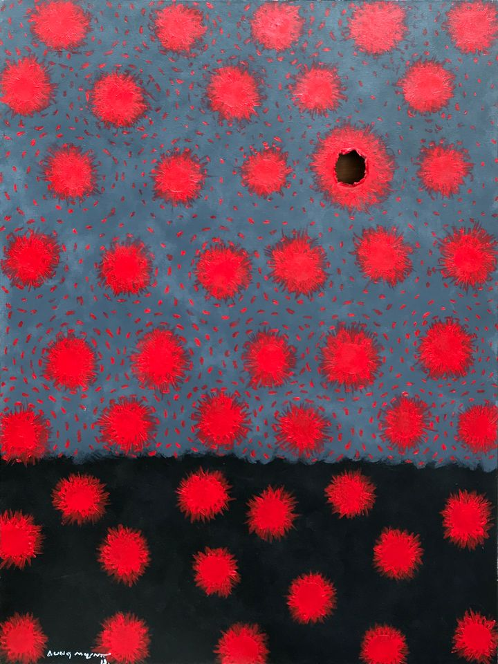 Against a grey background, globes of red are surrounded by specks of red, and a distinct hole shaped as a bullet hole is present on the surface of the canvas.