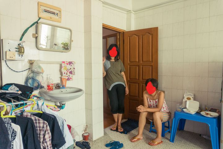 Two women are photographed in a domestic setting, one sitting on a stool while the other stands in a doorway. The two figures, likely women, have their faces covered by red blotches.