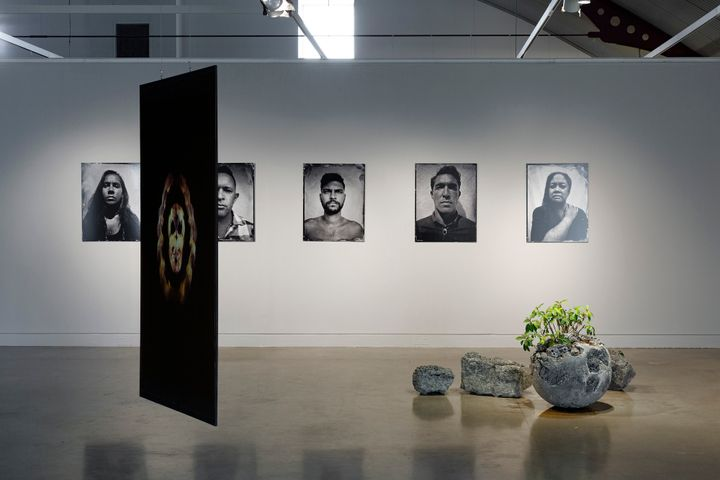 A series of five black and white portraits hang in a line on a  white wall in the gallery space, while a series of five stone sculptures are arranged in a cluster on the floor to the right, and a hanging video projection to the left features hands overlapping into a skull formation.