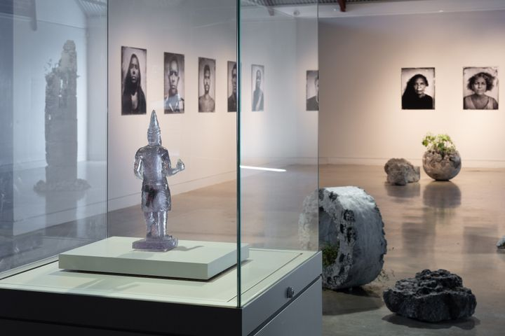 An installation shot of a gallery space shows portrait photographs hanging along the wall, with a silver figure on a pedestal in the foreground and three stone-like sculptures dotted along the floor.