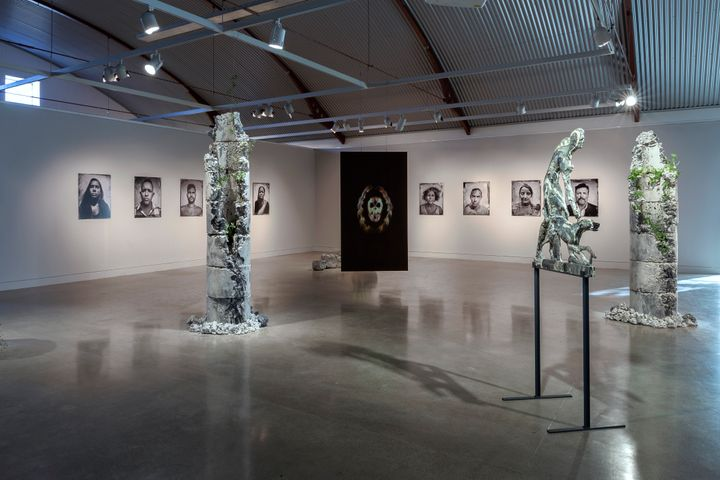 A photograph of at the gallery space features two walls with black and white portraits along them, while totem stone sculptures, plants coming out of their surface, are accompanied by a sculpture of a man and dog in the foreground.