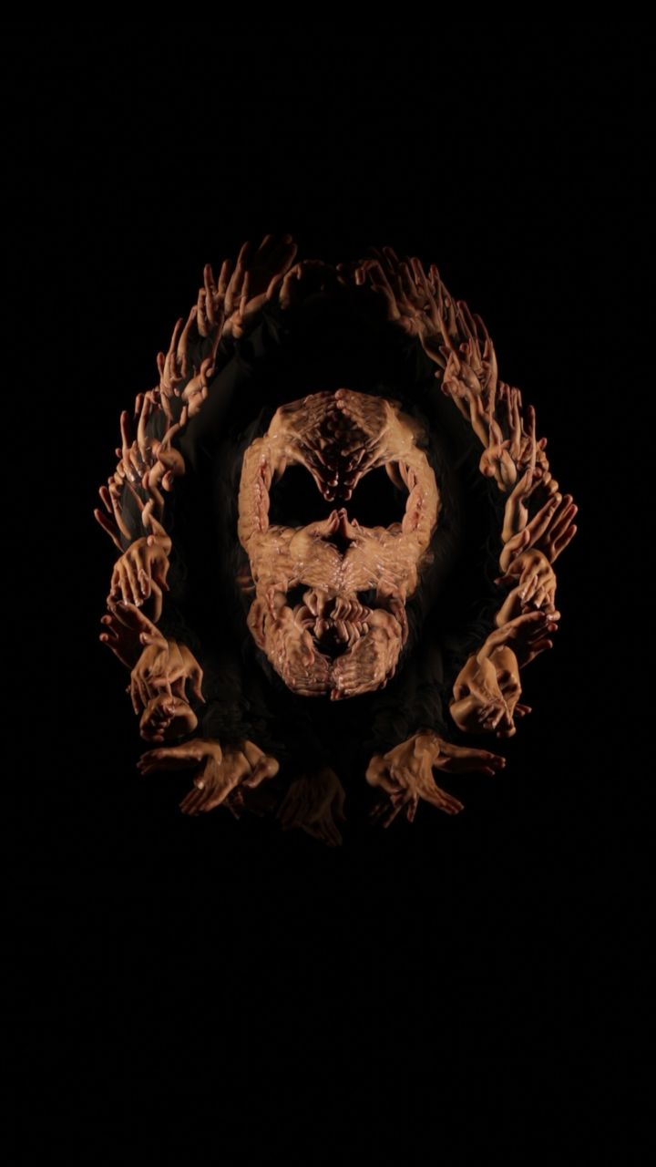 A video still features a series of hands that emerge from the darkness and overlap to create a skull formation.