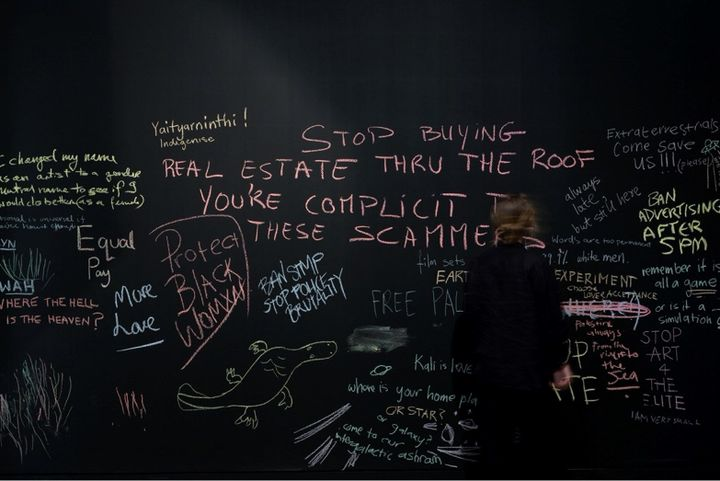 Words written in chalk on a backboard feature phrases such as 'Ban Advertising After 5PM' and 'Real Estate Through the Roof' and 'You're Complicit'