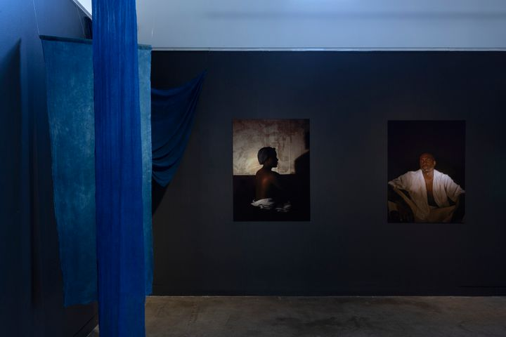 Two portraits hang on a blue wall in the gallery space to the right, while blue fabric hangs to the left.