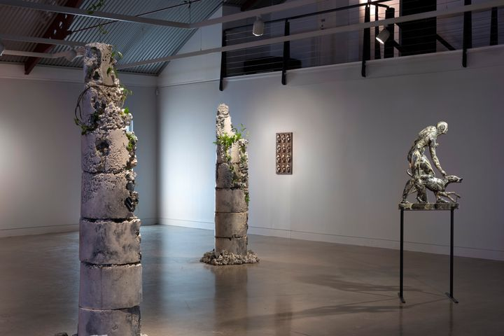 Two totem-like sculptures in stone are showing in the gallery space, with plants coming out from their sides, while to the right is a silver sculpture of a man and dog on a pedestal.