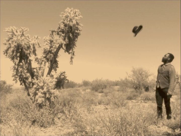 A sepia film still shows Samson Kambalu in a desert landscape, his hat suspended in the air beside him.