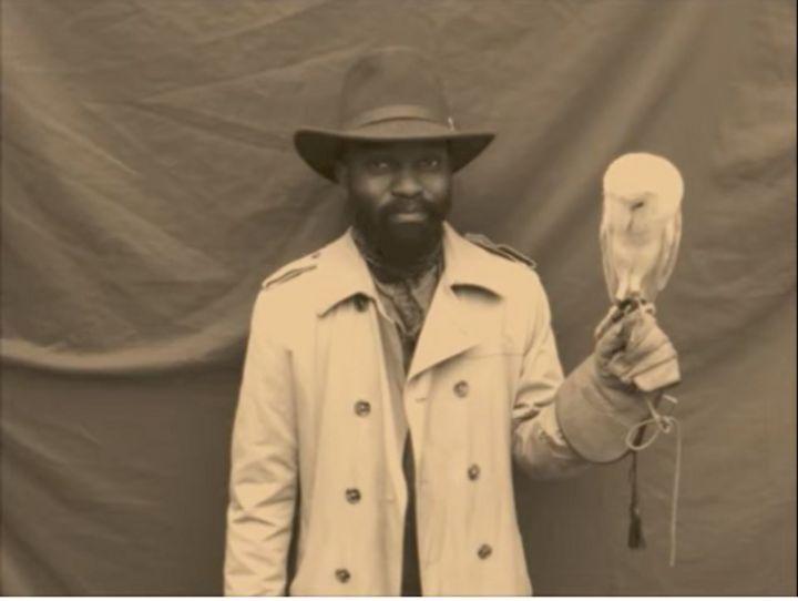 A sepia film still shows Samson Kambalu facing the camera. An owl sits upon his raised hand.