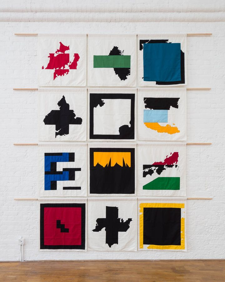 Twelve flags, each showing with abstract and geometric shapes, are hung in rows of three.