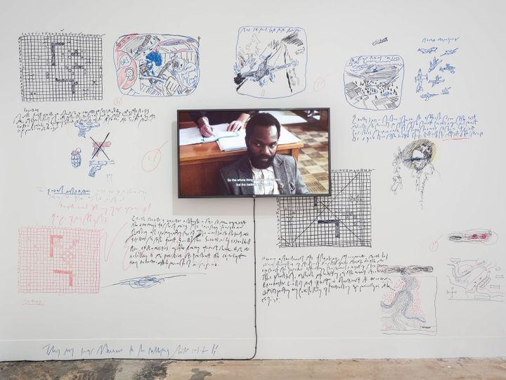 A white wall is filled with inscriptions and scribbles by Samson Kambalu, which surround a video on the wall that pictures the artist sitting in what appears to be a courtroom.