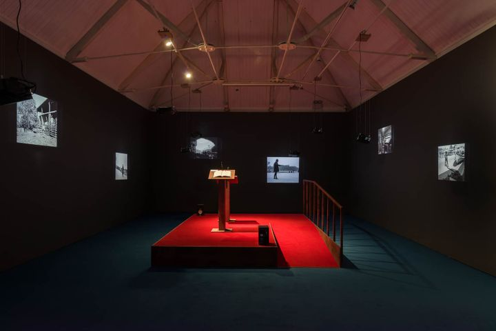 A podium with a red floor is illuminated in the centre of a darkened room. Across the black walls, video projections are arranged.