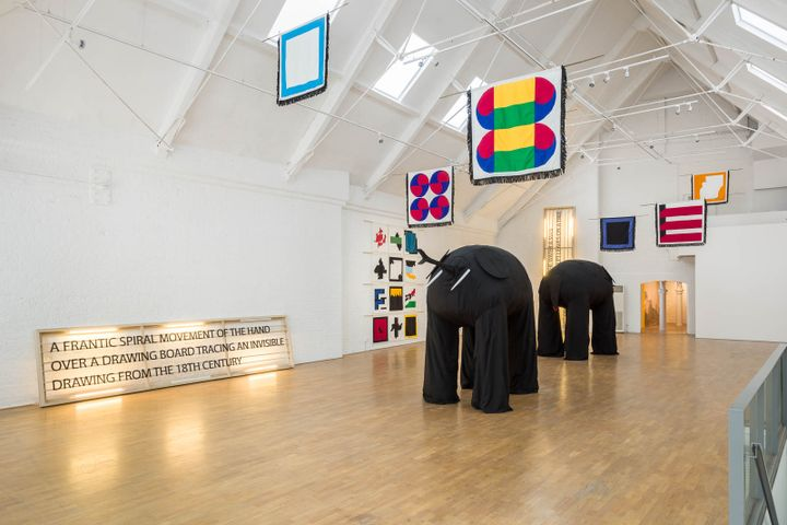 Samson Kambalu's exhibition at Modern Art shows two large black elephants in the middle of a white room with a high ceiling, which also contains abstract, geometric, and colourful flags hung around the space.