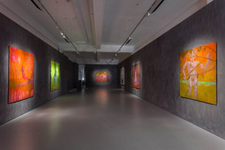Facing walls in a long, narrow gallery wall contain paintings in hues of red, orange, and green by Sedrick Chisom.