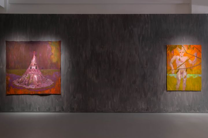 A painting of a burnt Tower of Babel in pink tones sits alongside a painting of a purple-tinted figure standing against a yellow and orange-hued landscape.