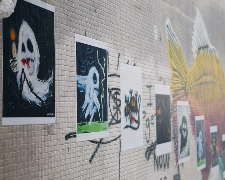 A street in Hong Kong features an outdoor exhibition of images of ghosts printed onto paper and stuck to the wall.