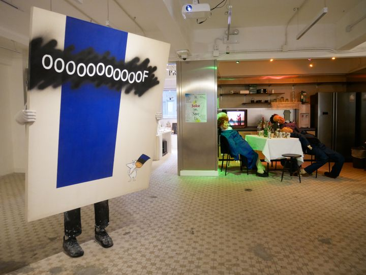 A painting with 'Oooof' written on its surface is held up by white-gloved hands, the figure behind it invisible apart from their feet. In the background of the exhibition space, a table with cans of beer on it is surrounded by dummies slouched on their chairs.