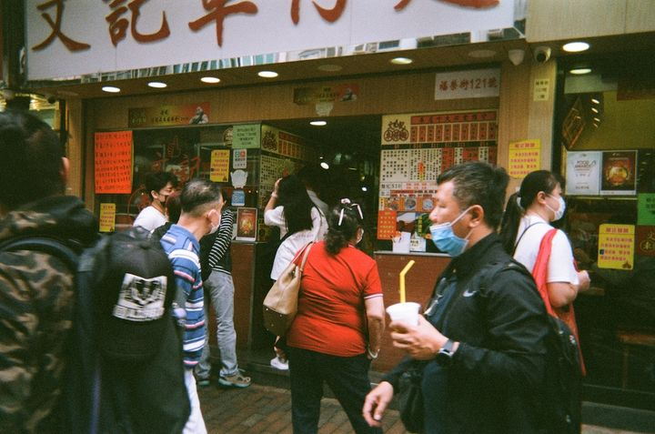 A busy street in Hong Kong, with people standing outside a restaurant, some wearing masks.