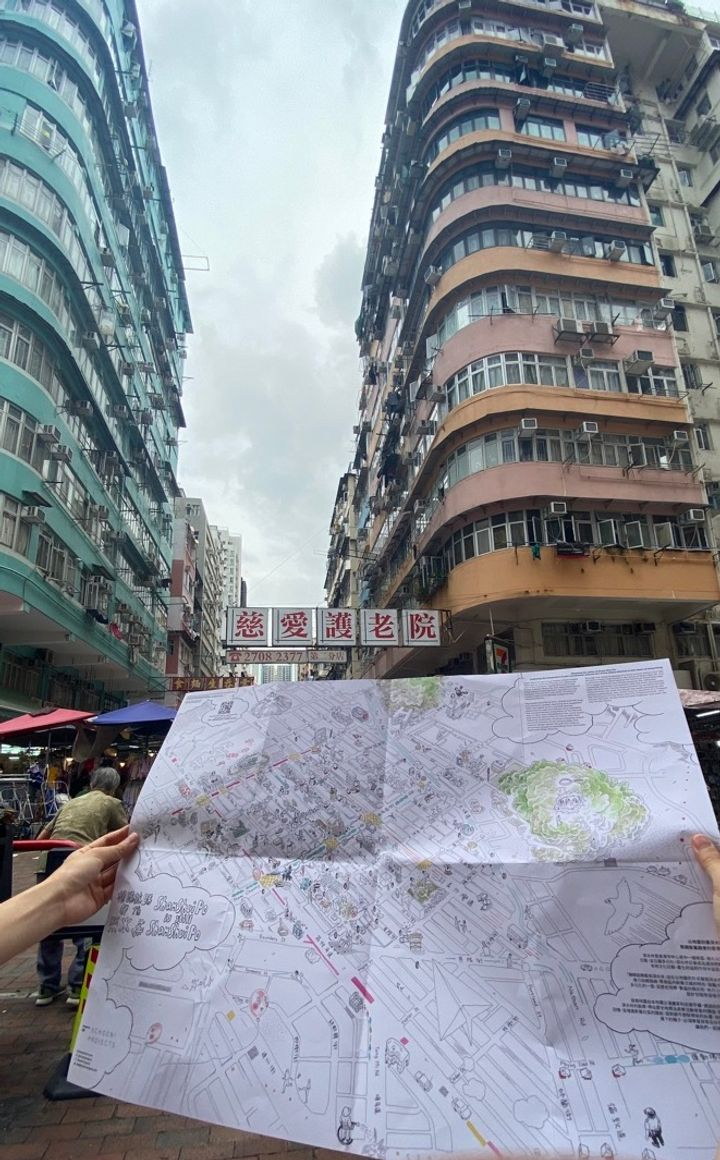 A map is held out beneath typical Hong Kong buildings from the 1980s in the city's Sham Shui Po district.