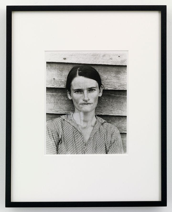 An iconic photograph from of Allie Mae Burroughs, a sharecropper's wife in 1930s Alabama, photographed during the Depression era. The photograph is surrounded by a black frame.