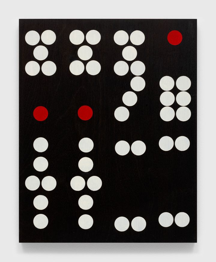 The face of a domino recreated on a mahogany panel by Sherrie Levine is photographed up close, its white and red dots standing out against a black background.