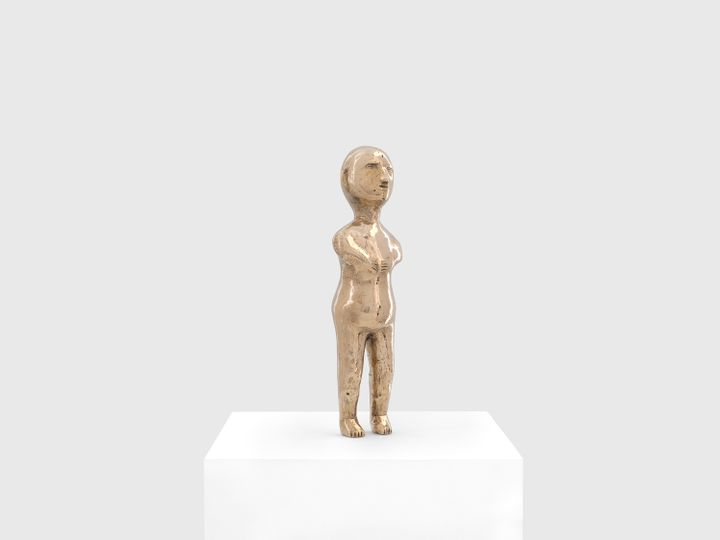 A Brazilian ex-voto figurine recreated by Sherrie Levine stands atop a pedestal in a white gallery space.