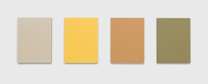 Four monochrome panels in tones of light brown, light green, and yellow are hung in a row on a white wall.