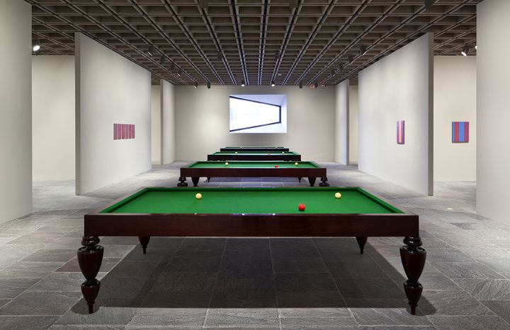 A row of pool tables stand in a large exhibition space.