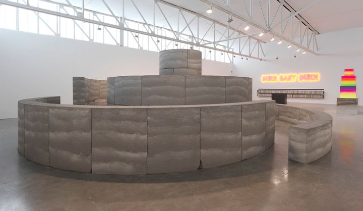 A labyrinthine structure, conical in formation, is made up of grey, rammed earth as part of an installation by David Adjaye. To the right in the background, some luminescent artworks are visible. Along the wall in the distance, neon signage reads 'Burn Baby Burn'.