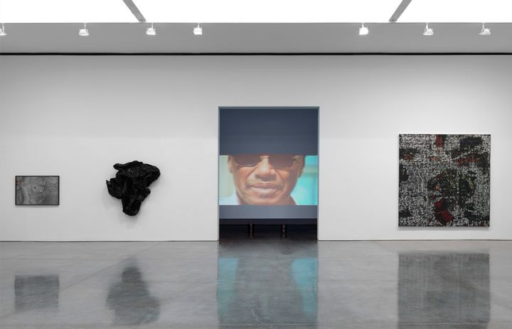 A wall in a gallery space features an opening that looks into a darkened room, where a video projection is showing. The video shows the face of a male figure wearing sunglasses. Back in the gallery space, the walls either side of the opening feature three artworks, including two geological wall sculptures to the left, and a painting by Rick Lowe to the right.