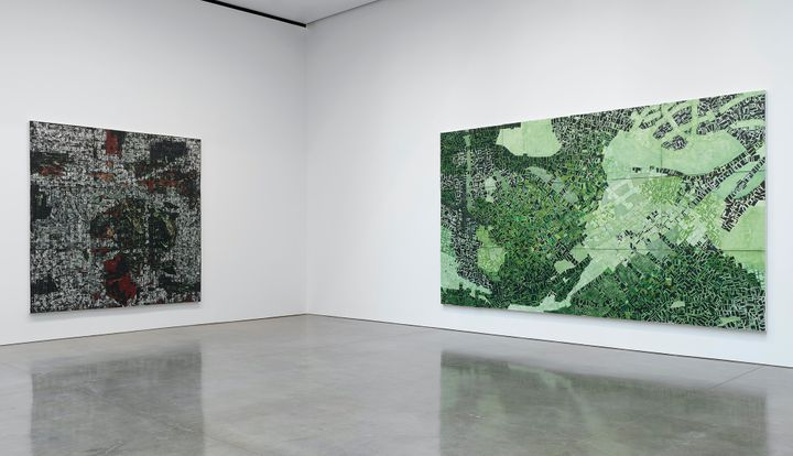 Two large-scale paintings by Rick Lowe are hung on flanking walls in the gallery space. They feature aerial views of Oklahoma's Greenwood District and are rendered in dark tones, one in black and white with dashes of green and red, and the other in green, black and white.