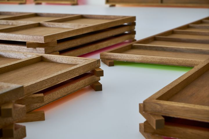 Plywood boards stacked upon one another lie across the gallery floor. The floor-facing sides have been painted shades of fluorescent pink and green, which glows from beneath the plywood.