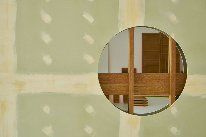 Gypsum board pasted with dots and lines of putty features a circle that has been embedded with a wooden structure embedded with mirrors. The assemblage resembles the section of a house in the midst of construction.