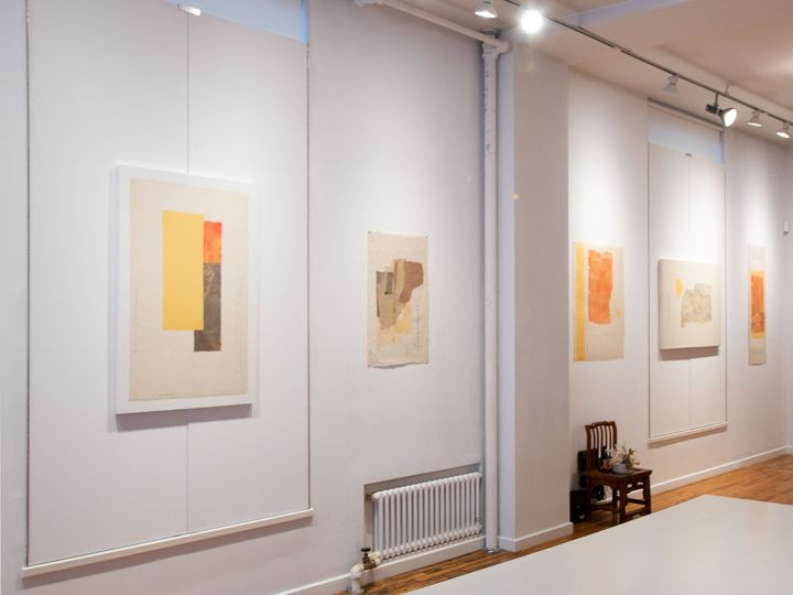 A series of collage paper works line the walls of the gallery. The works, by Wei Jia, feature tones of orange, yellow, and beige.
