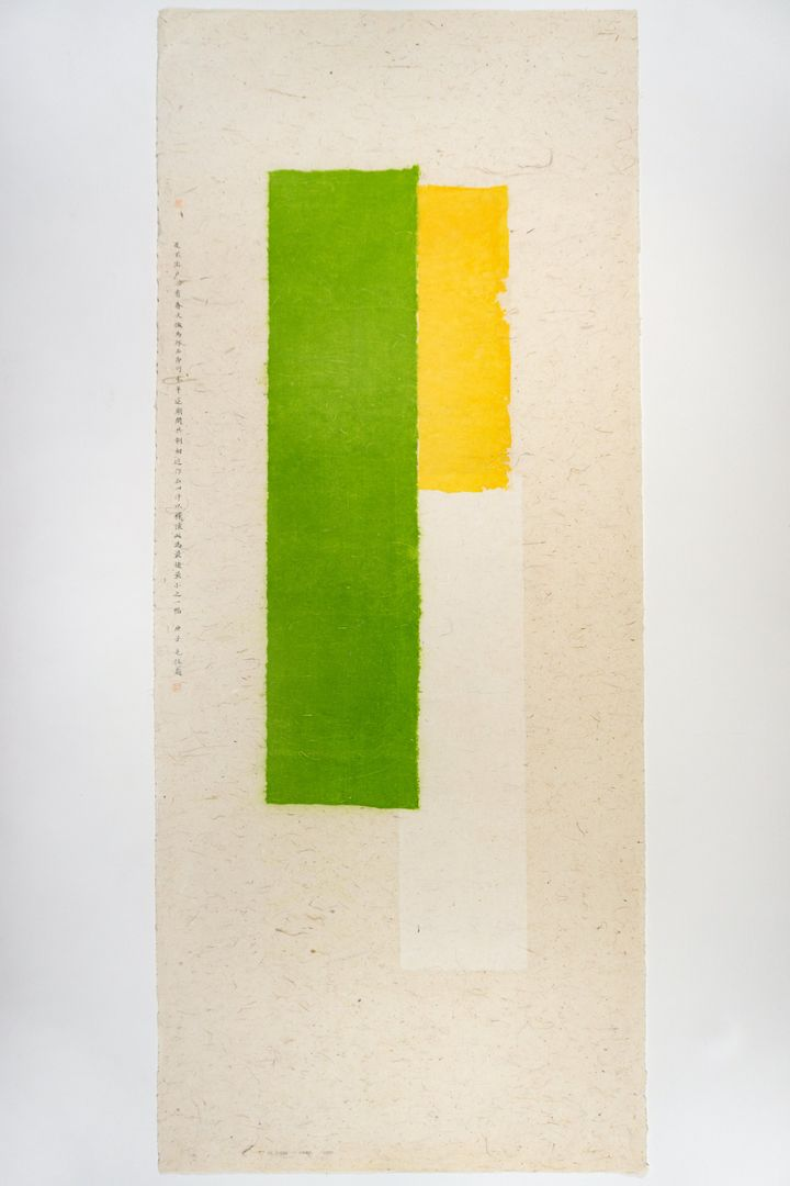 Three bars of green, yellow, and white are placed side by side on a length of beige paper in a collage by Wei Jia, while a column of Chinese characters sits to the left.