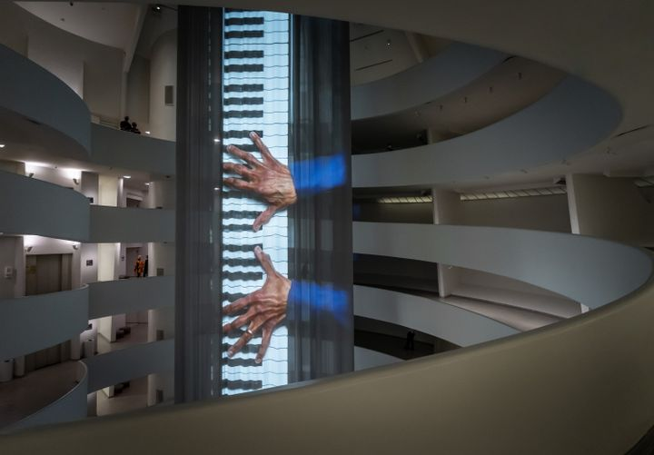 Inside the Guggenheim Museum hangs a long curtain projection of Wu Tsang's artwork portraying Glenn-Copeland singing while looking at his hands