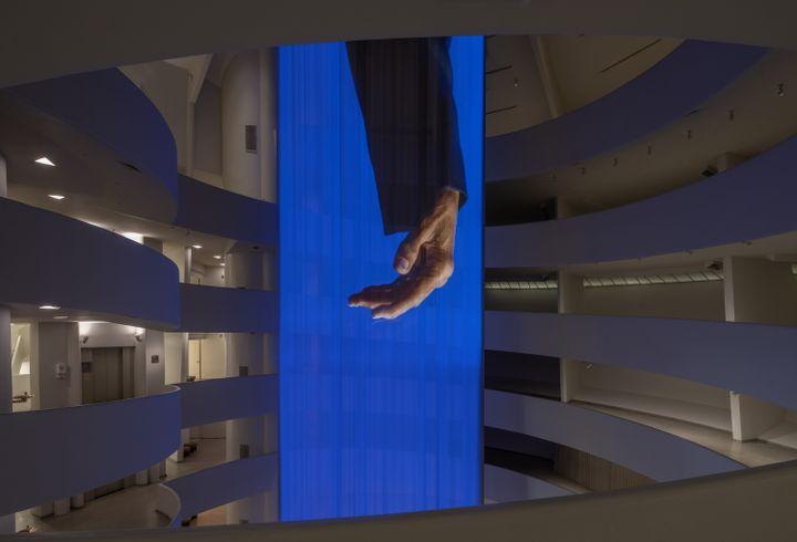 Inside the Guggenheim Museum hangs a long curtain projection of Wu Tsang's artwork portraying Glenn-Copeland's hand