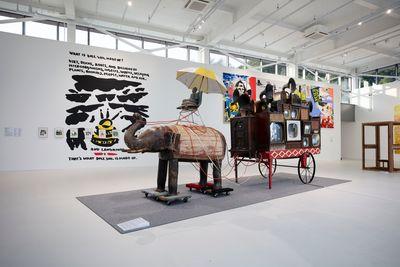 Nam June Paik, Elephant Cart (2001). Cart, elephant statue, limestone sitting Buddha statue, 22 CRT TV sets, telephone, phonograph, 4 dollies, umbrella, video distributor, wires, 2-channel video, colour, silent, DVD. 293 x 633 x 153cm. Nam June Paik Art Centre. Photo: Kim San.