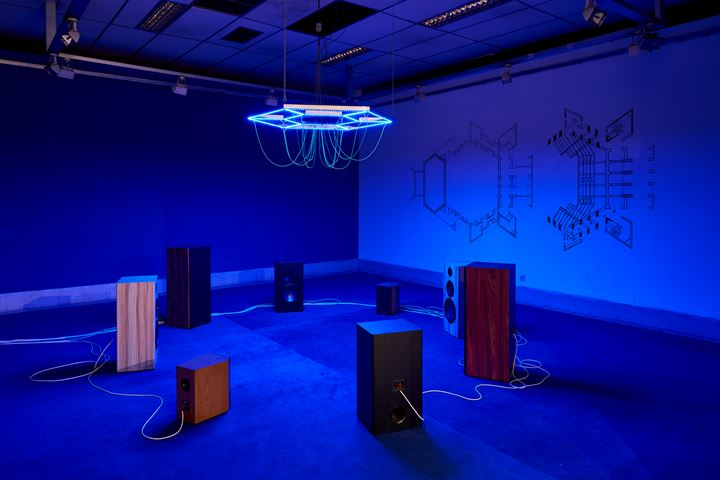Haroon Mirza, A Lesson in Theology (2019–2020). 24-channel electrical signals for Hi-Fi speakers and LEDs, steel, electrical wire, bespoke media device, carpet, and wall painting. Exhibition view: Seismic Movements, Dhaka Art Summit, Shipakala Art Academy (7–15 February 2020). Commissioned and produced by Samdani Art Foundation and Lisson Gallery for DAS 2020. Courtesy the artist, Samdani Art Foundation, and Lisson Gallery. Photo: Randhir Singh.