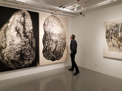 Artist Herwig Kempinger inspects a work on view in Faizal Suhif: Visual Poetry, G13 Gallery, Kuala Lumpur (16–30 December 2017).