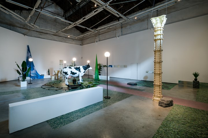 Nabuqi, Do real things happen in moments of rationality?  (2018). Electronic controller, spray-painted FRP cow model, flat car, battery, stainless steel track, outdoor spherical lamp, artificial plant, foam stone, PVC column, inkjet cloth curtain, mirror. 540 x 1600 x 1400 cm. Exhibition view: Nabuqi, Do real things happen in moments of rationality?, ShanghART M50, Shanghi (27 October–9 December 2018). Courtesy ShanghART.