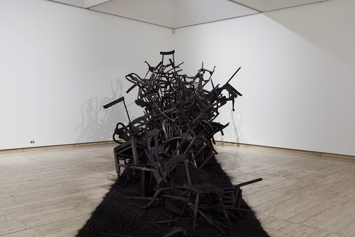 Rushdi Anwar, Irhal (Expel), Hope and the Sorrow of Displacement (2013–ongoing). Burnt wooden chairs, black oxide pigment, charcoal, ash. Dimensions variable. Exhibition view: The National 2019: New Australian Art, Art Gallery of New South Wales, Sydney (29 March–21 July 2019). © Rushdi Anwar. Courtesy the artist. Photo: AGNSW, Mim Stirling.