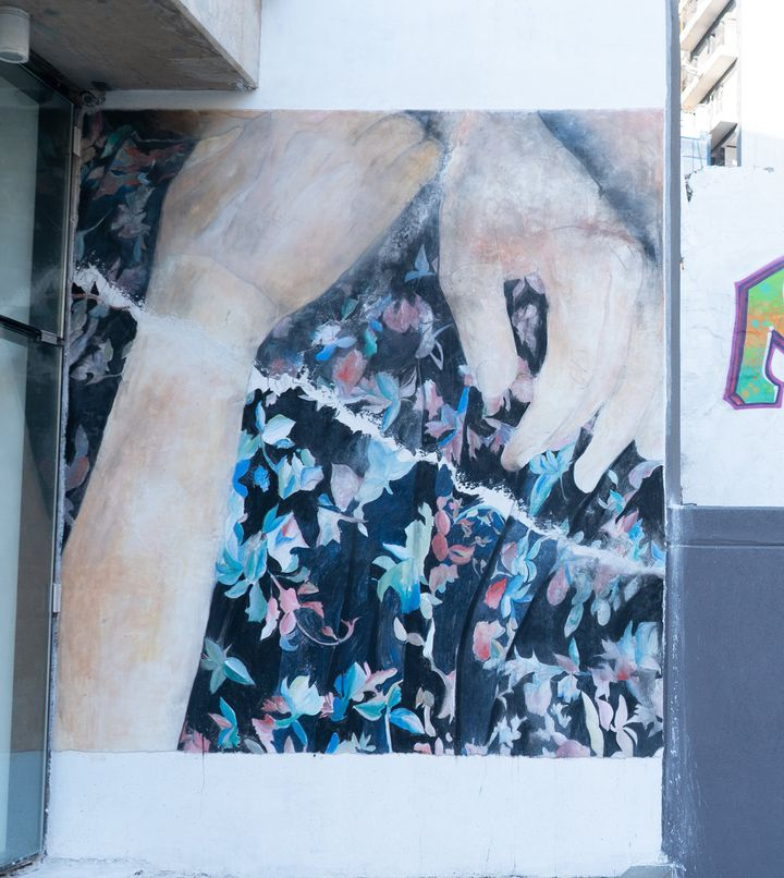 A pair of hands are painted on a mural outdoors, cradling what appears to be a painting of black fabric with blue and red flowers adorning it. The mural is showing outside Galerie Tanit.