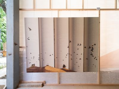 A series of silos is photographed with a sand bank against it, with birds fluttering across the photograph. Shot by Dia Mrad, the photograph is blown up large-scale and placed against a wooden frame in a semi-outdoors space.