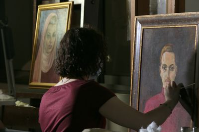 A woman is photographed restoring a painting in the lab of the Sursock Museum. The painting features a male figure staring out of the picture plane.