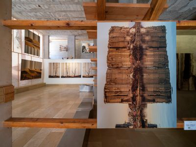 Photographs by Dia Mrad photographing the aftermath of the 2020 port blast are shown in Arthaus. The gallery space resembles a construction space, with photographs hung on wooden framework.